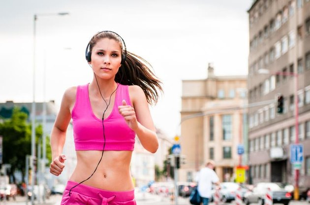 Young beautiful woman with headphones jogging and listening music in street