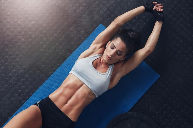 Overhead shot of muscular and fit young woman doing stretching workout exercise mat. Fitness female lying on mat with stretching her hands.
