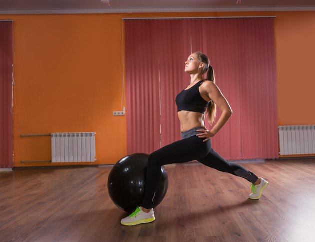Young Woman Doing Leg Lunges in Exercise Studio