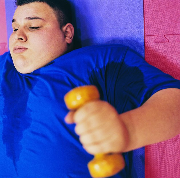 Young Man Lying on an Exercise Mat Lifting a Dumbbell