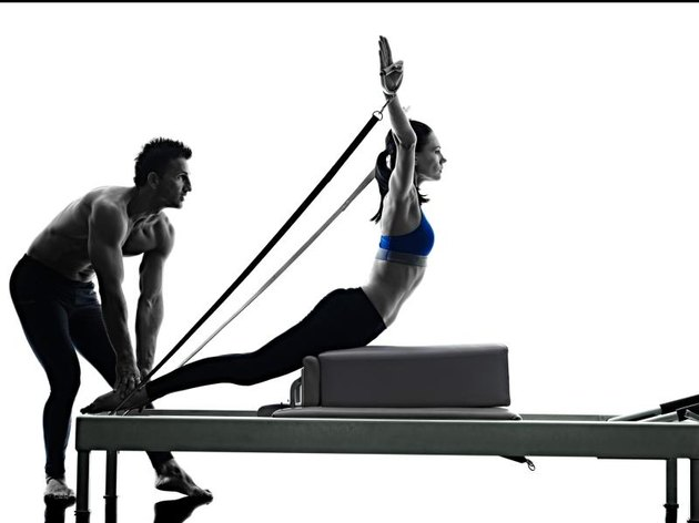 one caucasian couple exercising pilates reformer exercises fitness in silhouette isolated on white backgound