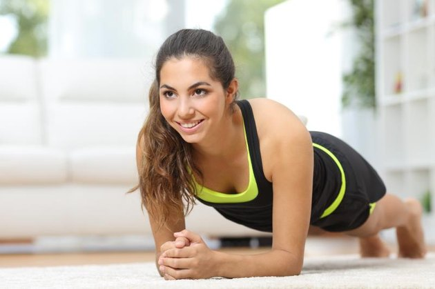 Happy fitness woman practicing sport on the floor at home