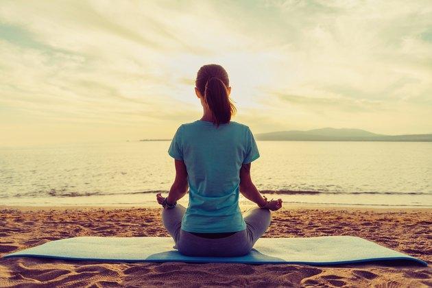 Girl meditating in pose of lotus on beach
