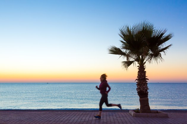 Young Woman jogging on Seafront making Morning Fitnes