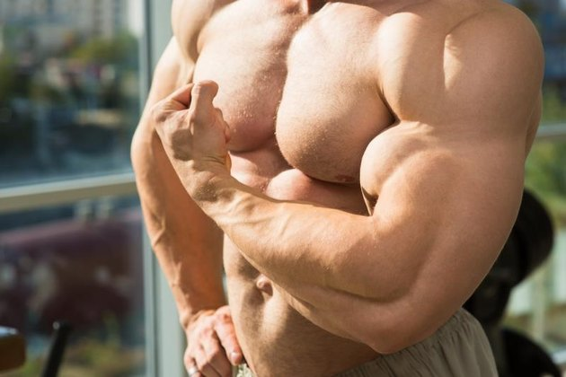Muscular torso and arms. Bodybuilder with huge muscles. Strong man's torso. Picture of muscular torso, arms and abs.