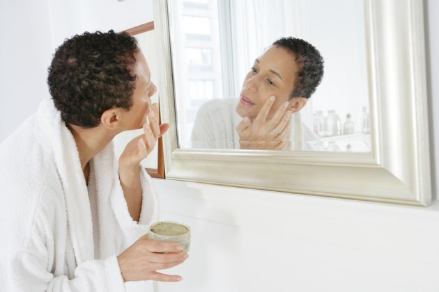 African American woman applying face mask.