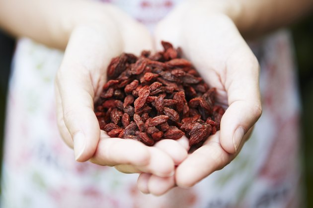 Woman Holding Handful Of Goji Berries