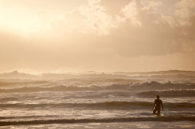 Surfer and waves at sunset