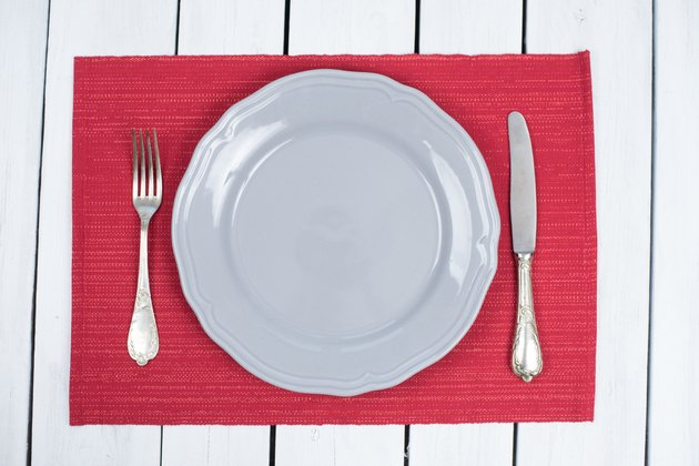 Empty Grey Plate on a red placemats with silverware