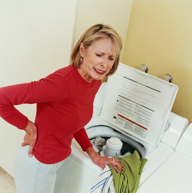 Injured Mature Woman Loading a Washing Machine and Holding Her Back in Pain