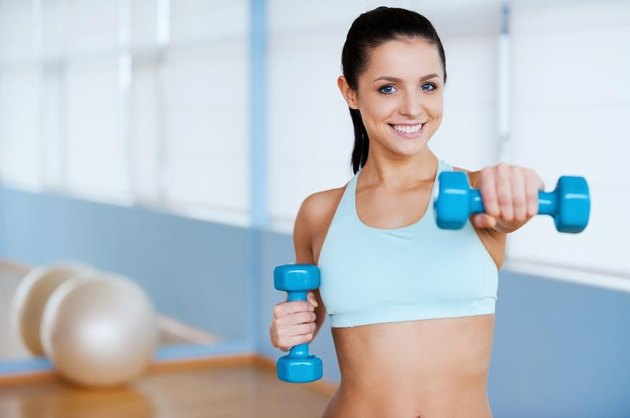 Beautiful young woman in sports clothing exercising with dumbbells and smiling while standing in health club