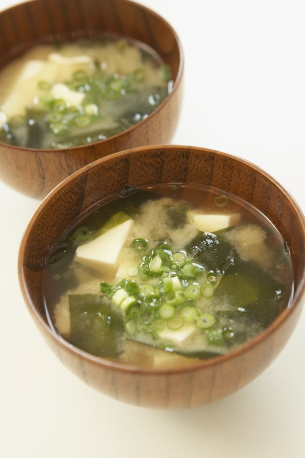 Tofu and seaweed in Miso soup, close up, white background