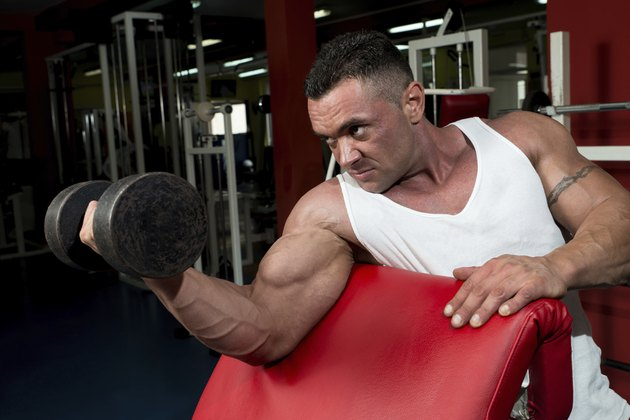 Man In The Gym Exercising Biceps With Dumbbells