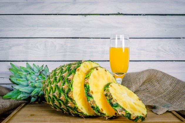 Pineapple and juice on a wooden board