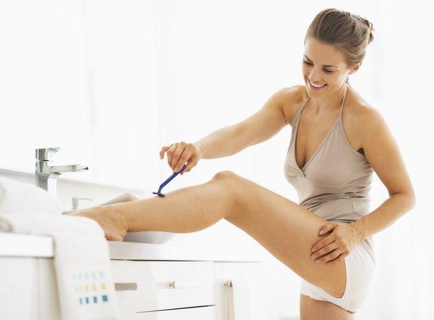 Woman shaving legs in bathroom