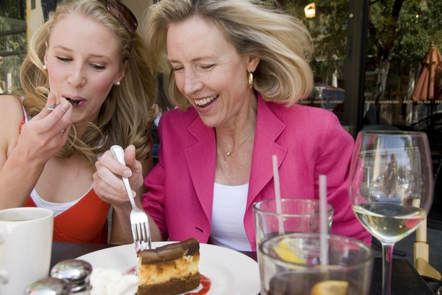 Mature woman sharing slice of cheesecake with her daughter