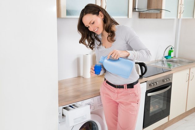 Woman Pouring Liquid Detergent In The Bottle Cap