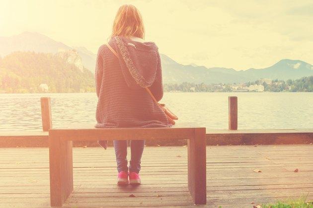 Girl sitting on a wooden pier near water.
