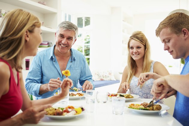 Family With Teenage Children Eating Meal At Home Together