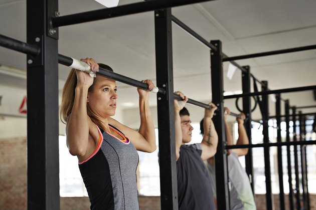 Woman & 2 men doing pull-up's at gym gym