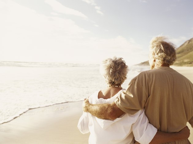 Rear View of a Senior Couple Standing on a Beach With Their Arms Around Each Other