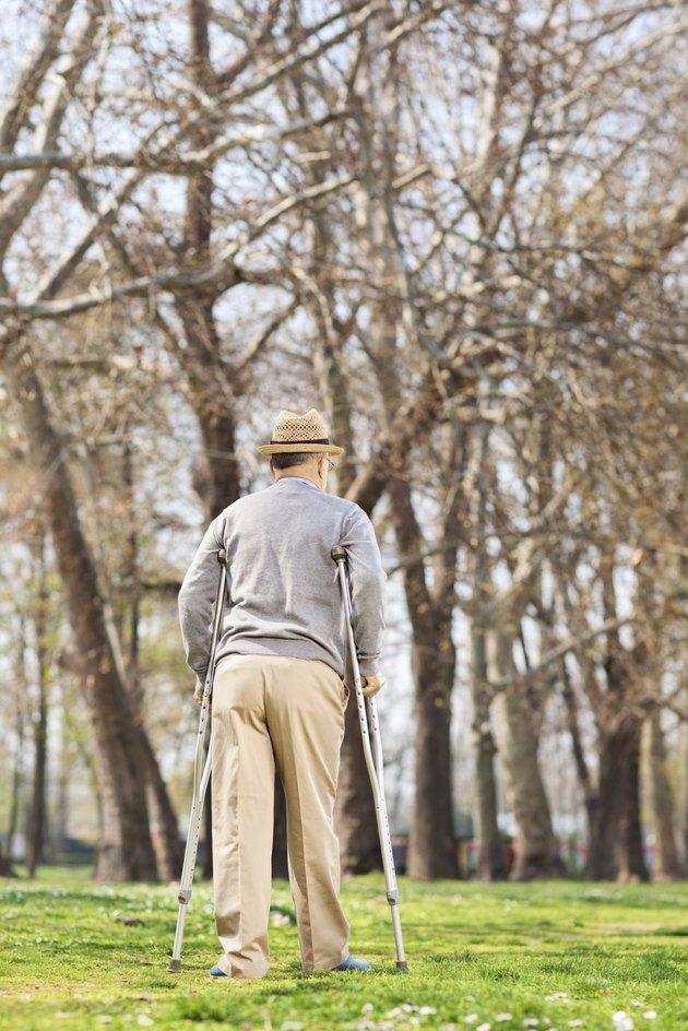 Elderly gentleman with crutches, walking in park
