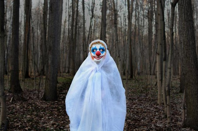 Evil clown in a mask standing in a dark forest in a white veil.