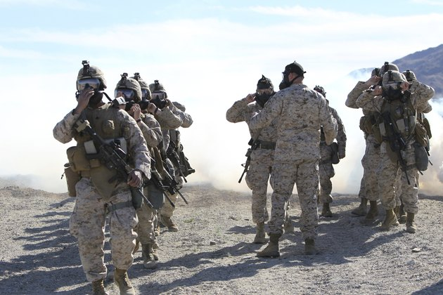 Marines and sailors participate in an outdoor gas exercise in full protective gear.