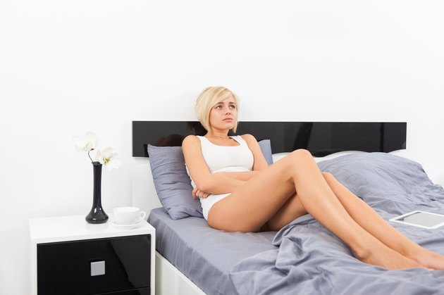 stomach ache, woman lying on bed