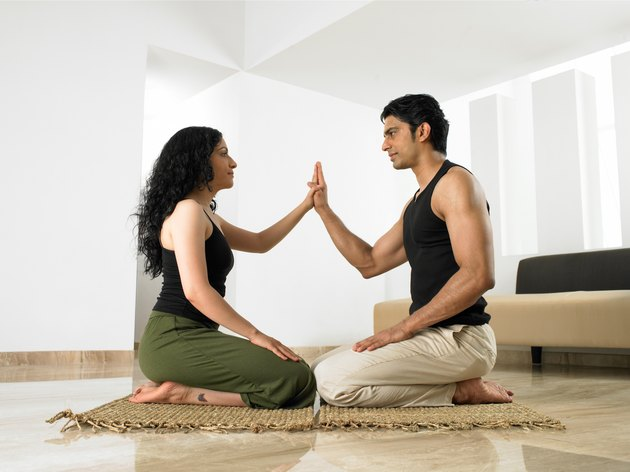 Couple in yoga position touching palms, side view
