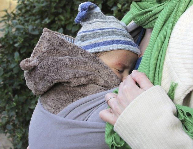 Sleeping baby in a slings - wedding ring on finger