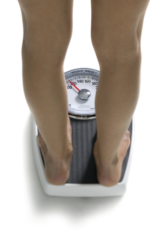 conceptual shot of the legs of a young adult woman as she stands on a bathroom scale