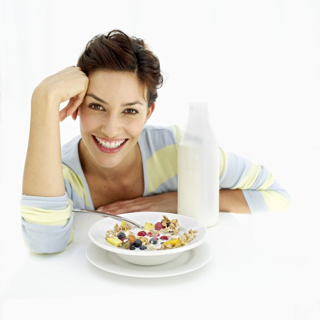 portrait of a young woman sitting with a bowl of breakfast cereal and milk