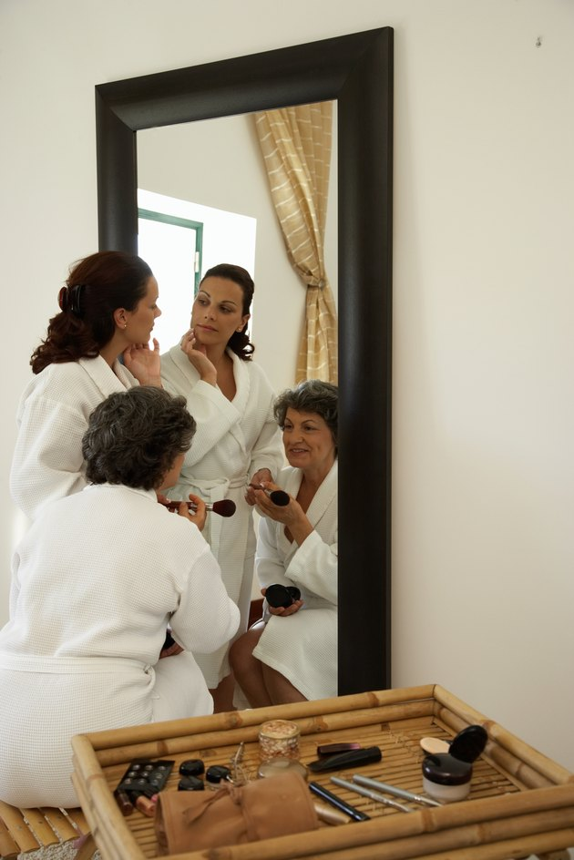 Two women in bathrobes applying make-up, looking in mirror
