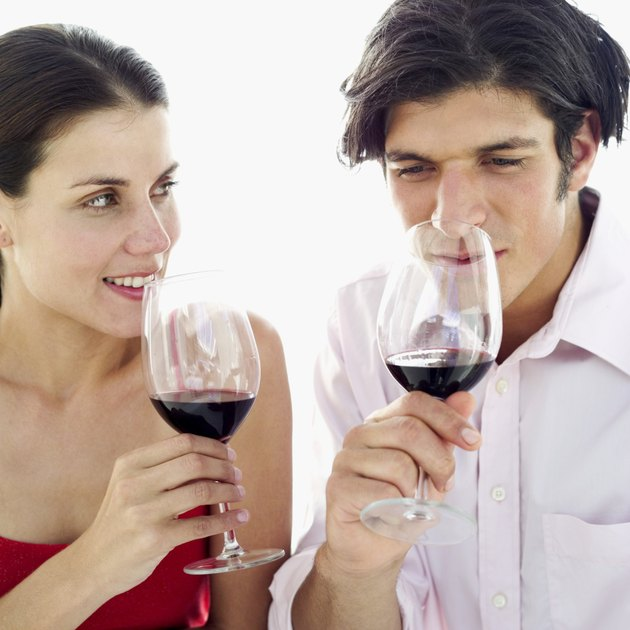 close-up of a couple smelling the aroma of red wine