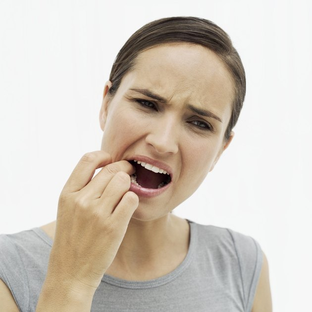 woman feeling her tooth with her finger