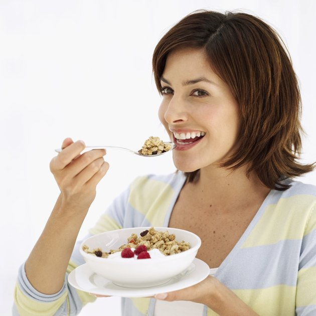 side view of a woman eating a bowl of cereal