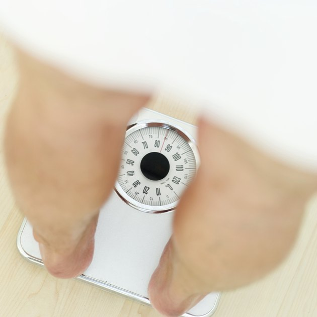 close-up of a mans legs standing on a weighing scale