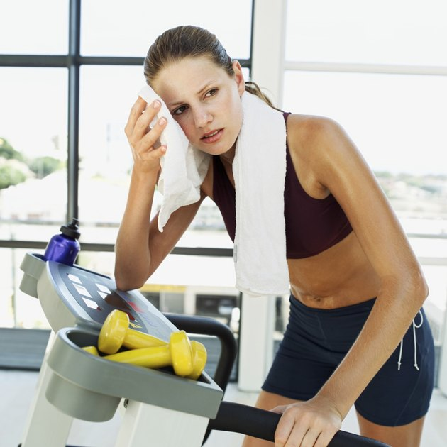woman standing on a treadmill and wiping her face