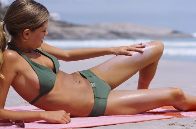 Young woman lying on the beach applying suntan lotion on her leg