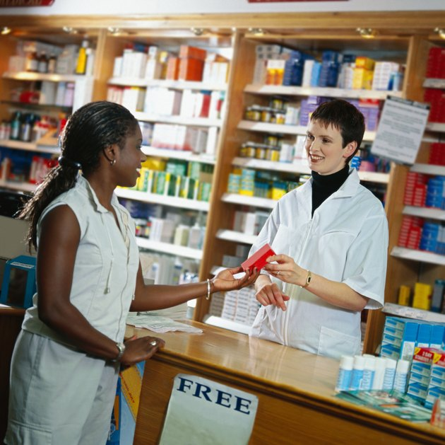 portrait of a young sales woman handing a product to a female customer