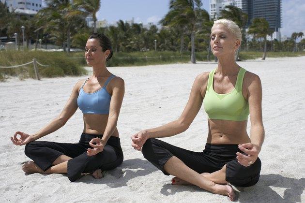 Two women doing yoga on beach