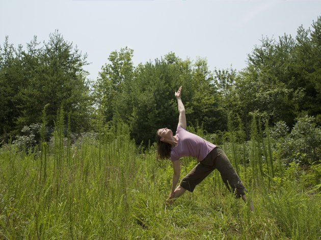 Mature woman stretching on meadow