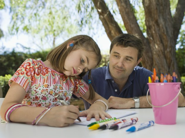 Girl drawing as father watches