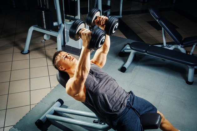 Young man at the gym chest workout with dumbbells
