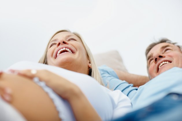Smiling pregnant couple lying together in bed