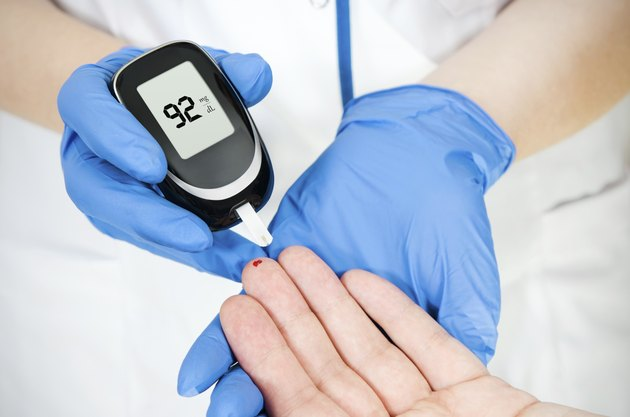 Doctor woman measuring glucose level blood in hospital close-up
