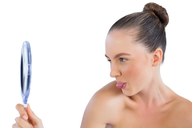 Woman looking in the mirror and sticking tongue out