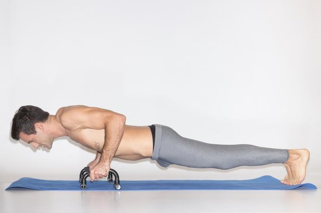 young man exercise push ups bar. white background, studio, yoga mat, simple.