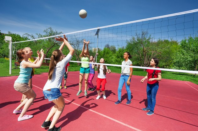 Teenage girls and boy play together volleyball